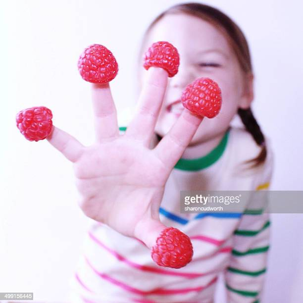 Girl (4-5) showing raspberries on fingers