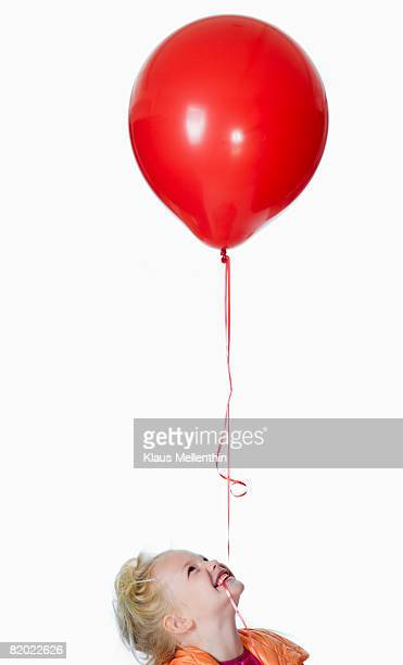 Girl (8-9) with balloon in mouth, close-up