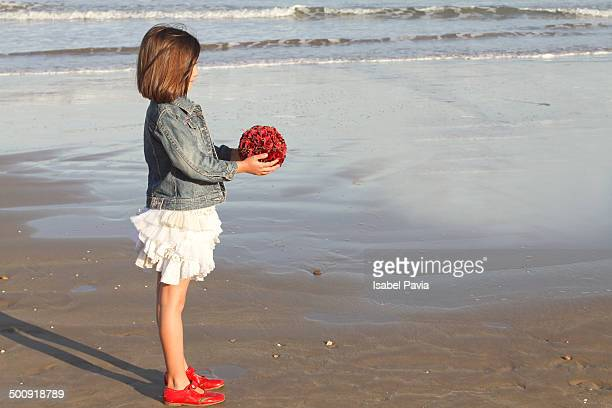 Girl with red bouquet in front of the sea