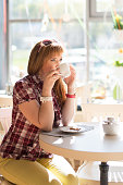 A girl with red hair sits in a summer cafe with a cup of coffee. European with fair skin