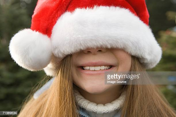 Girl with santa hat covering eyes