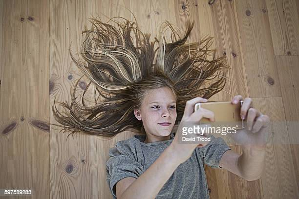 Girl with smart phone lying on a woodern floor.