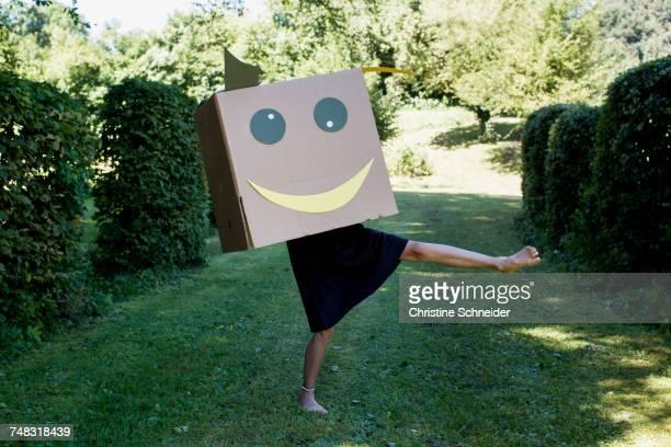 Girl with smiley face box over head