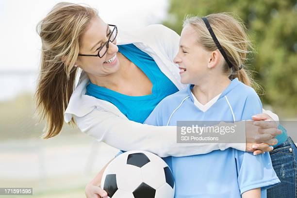 Girl with soccer ball embraced and smiling with older woman.