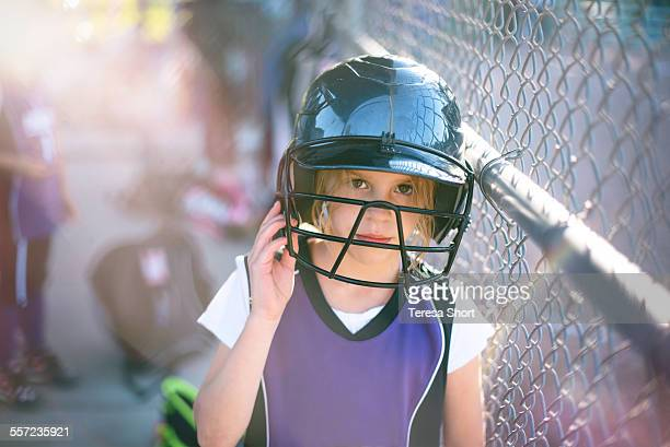 Girl with softball helmet in dugout