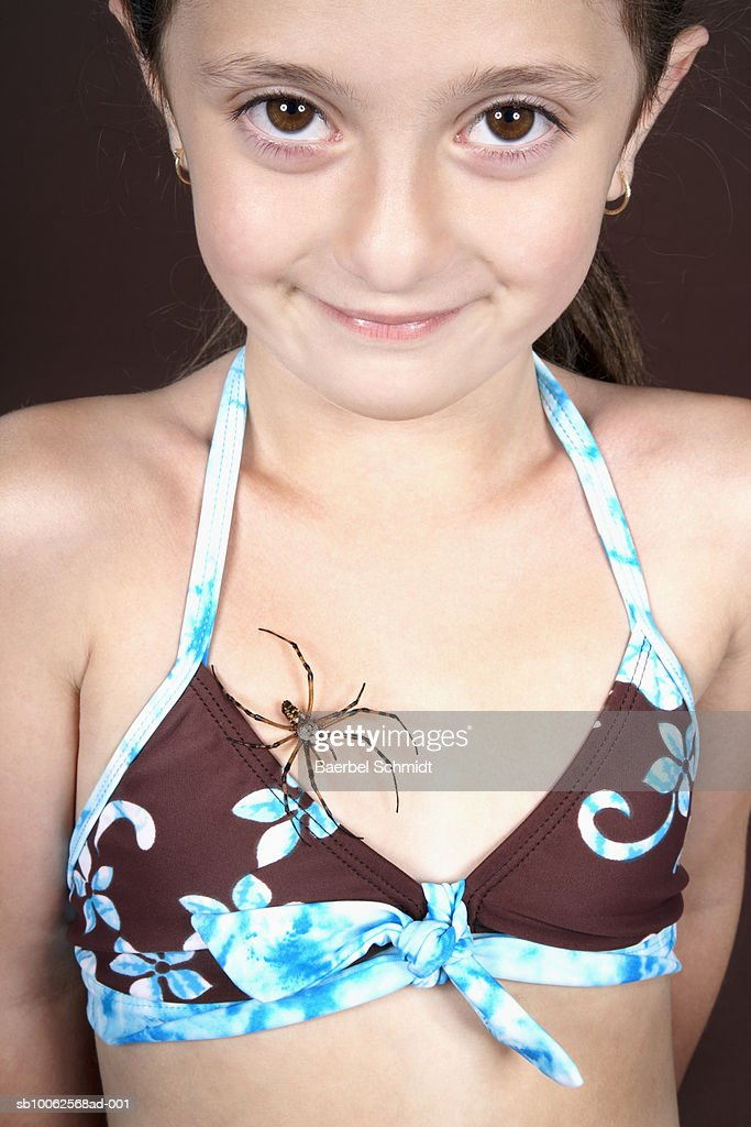 Girl (6-7) with spider crawling on chest, portrait, close-up : Stock Photo
