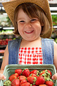 Girl (3-5) with strawberries in market smiling, portrait, close-up