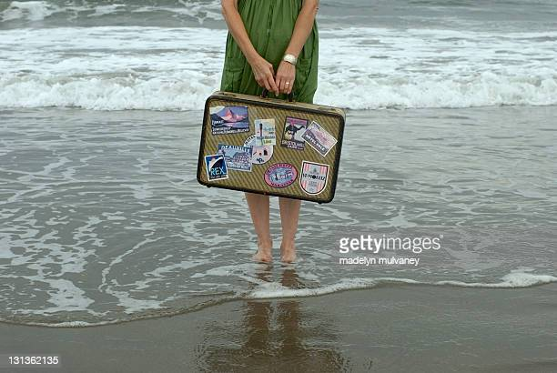 Girl with suitcase in sea