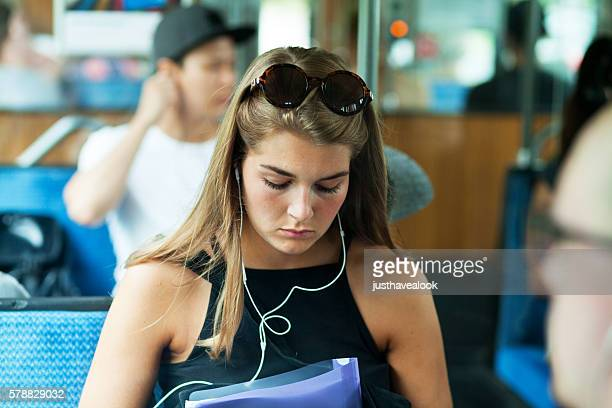Girl with sunglasses and earphones in tram