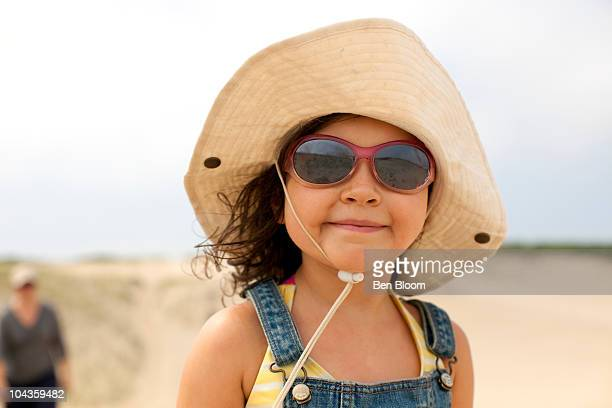 Girl with sunglasses and hat at beach.