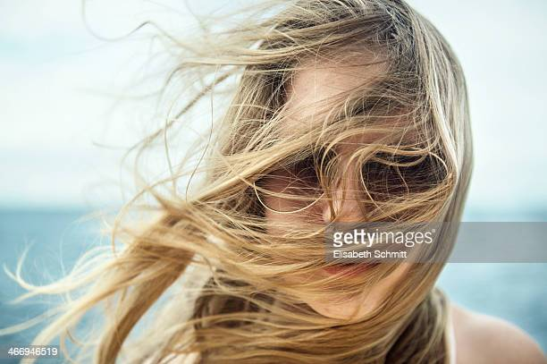 Girl with sunglasses, hair blowing up by wind