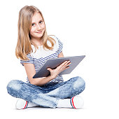 Girl with tablet. Cute  little schoolgirl with a tablet PC.