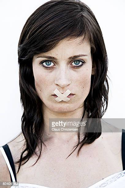 girl with tape over her mouth