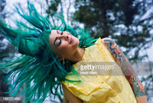Girl with tattoos flipping green hair