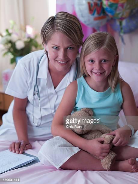 Mädchen mit Teddybär und Krankenschwester im Krankenhaus