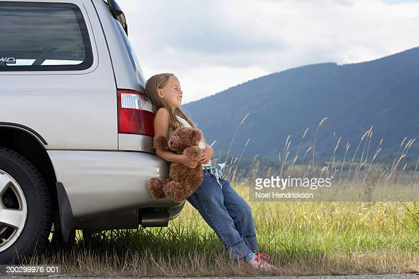 Girl (5-7 years) with teddy bear leaning against car, side view