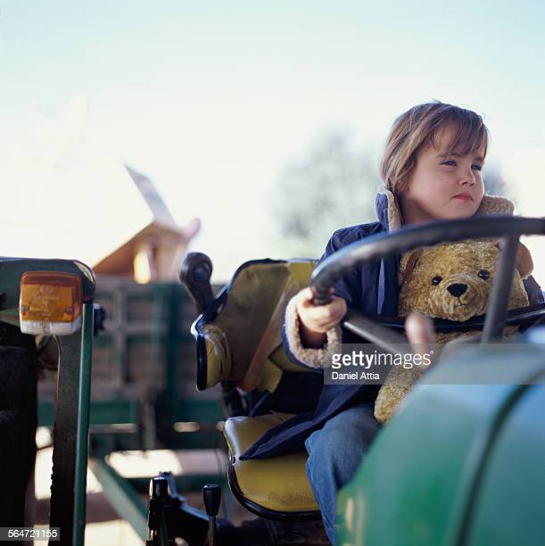 Girl with Teddy Bear Sitting on Tractor
