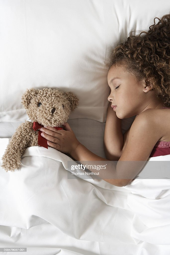 Girl (5-7) with teddy bear sleeping in bed, overhead view : Stock Photo