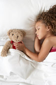Girl (5-7) with teddy bear sleeping in bed, overhead view