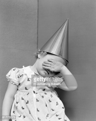 Girl With The Back Of Her Hand Covering Her Face Sitting In A Corner Wearing A Cotton Print Dress With White Lace Collar & Dunce Cap On Her Head.