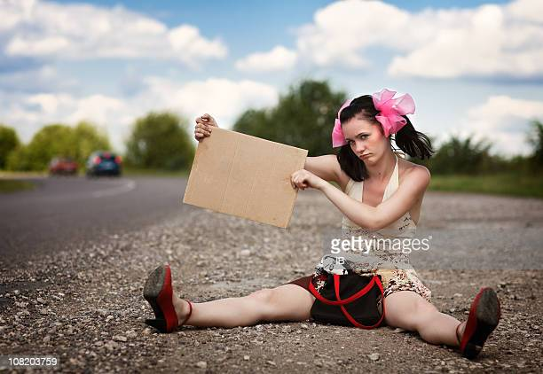 Girl with the blank sign sits on a roadside