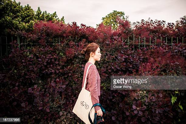 A girl with tote bag is walking in a park