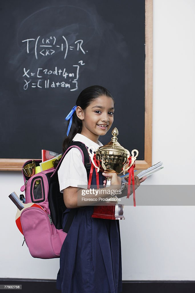 Girl with trophy by blackboard in classroom : Stock Photo