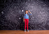 Girl in blue striped t-shirt and red trousers, with two braids, arm raised, finger raised, against big blackboard with mathematical symbols and formulas