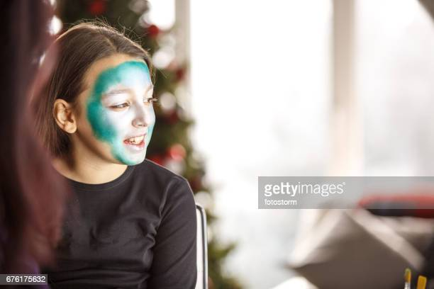 Girl with unfinished face paint during Christmas party