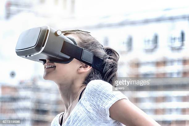 girl with virtual reality simulator in city