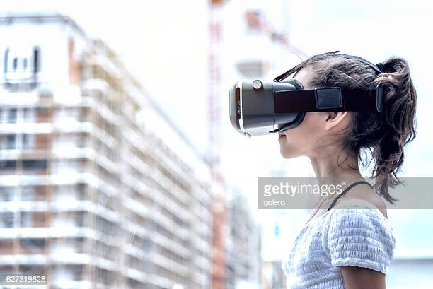 girl with virtual reality simulator with blurred city background