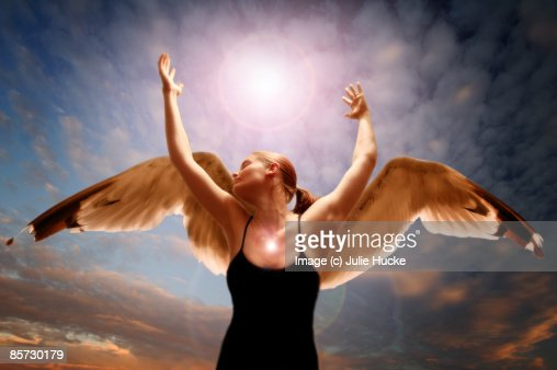 Girl with wings raises hands to sky
