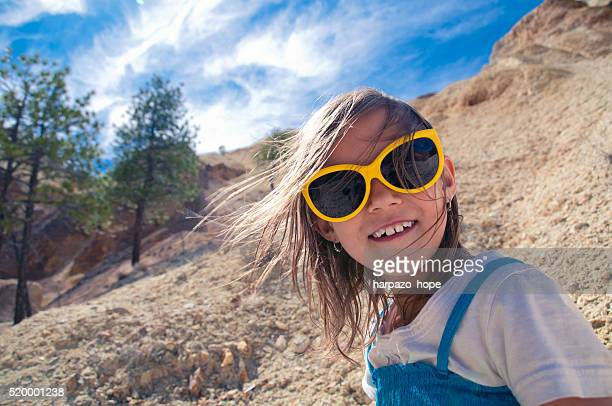 Girl with yellow glasses in a desert landscape.