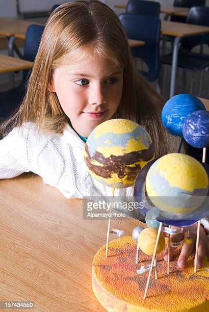 Girl working with space models in the classroom