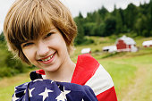 Girl wrapped in American flag on farm