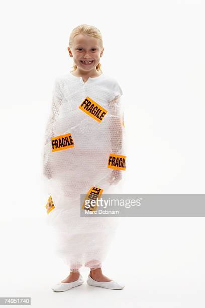 Girl (7-9) wrapped in bubble wrap labelled fragile, smiling, portrait