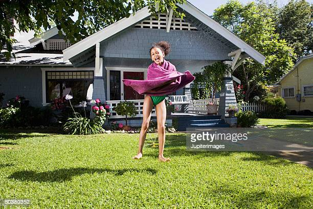 Girl wrapped in towel leaping in front of house