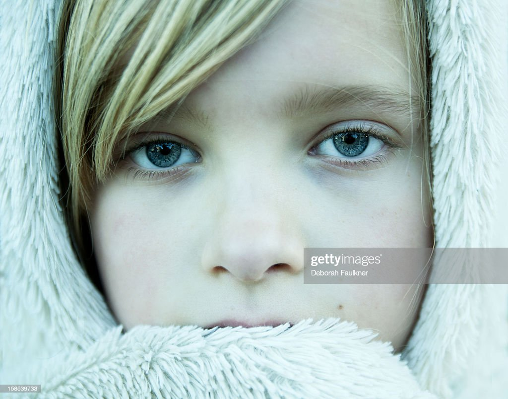 Girl wrapped up in white furry coat : Stock Photo
