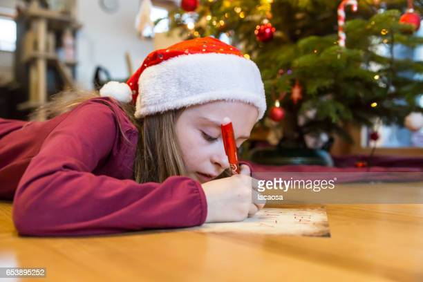 girl writing a letter to Santa Claus in front of a christmas tree