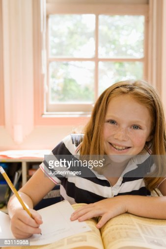 Girl writing in book on desk at classroom stock photo