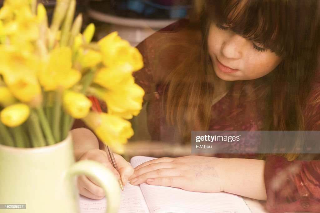 Girl writing by daffodils on desk : Stock Photo