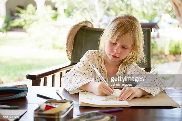 Girl writing in garden
