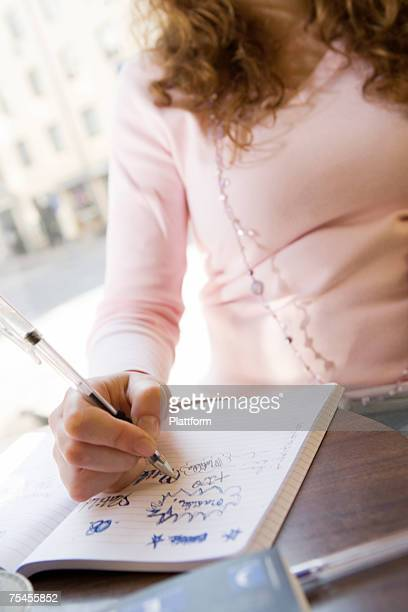 A girl writing in her note book in a cafe.
