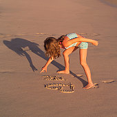 Girl writing in the sand on beach in Costa Rica