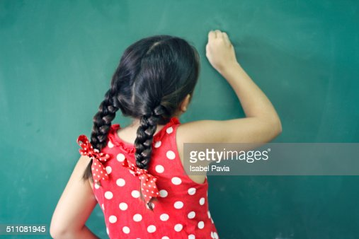 Girl writing on a chalkboard at school