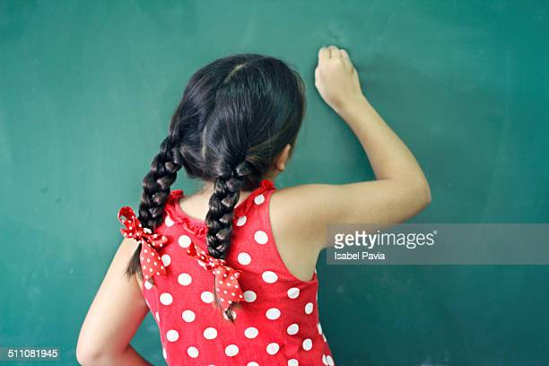 Girl writing on a chalkboard at school