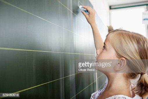 Girl writing on blackboard : Stock Photo