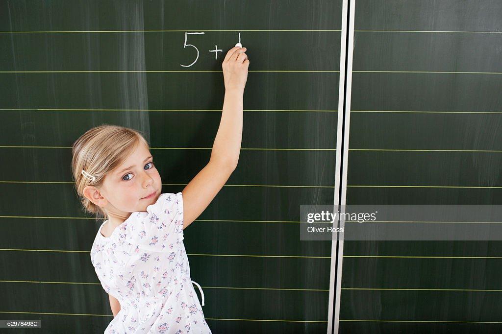 Girl writing on blackboard : Bildbanksbilder