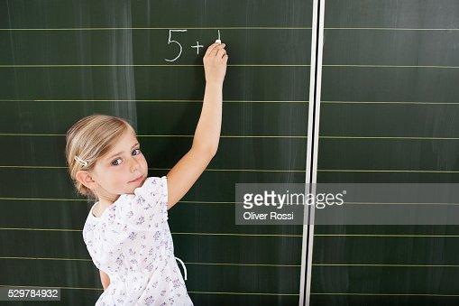 Girl writing on blackboard : Stockfoto