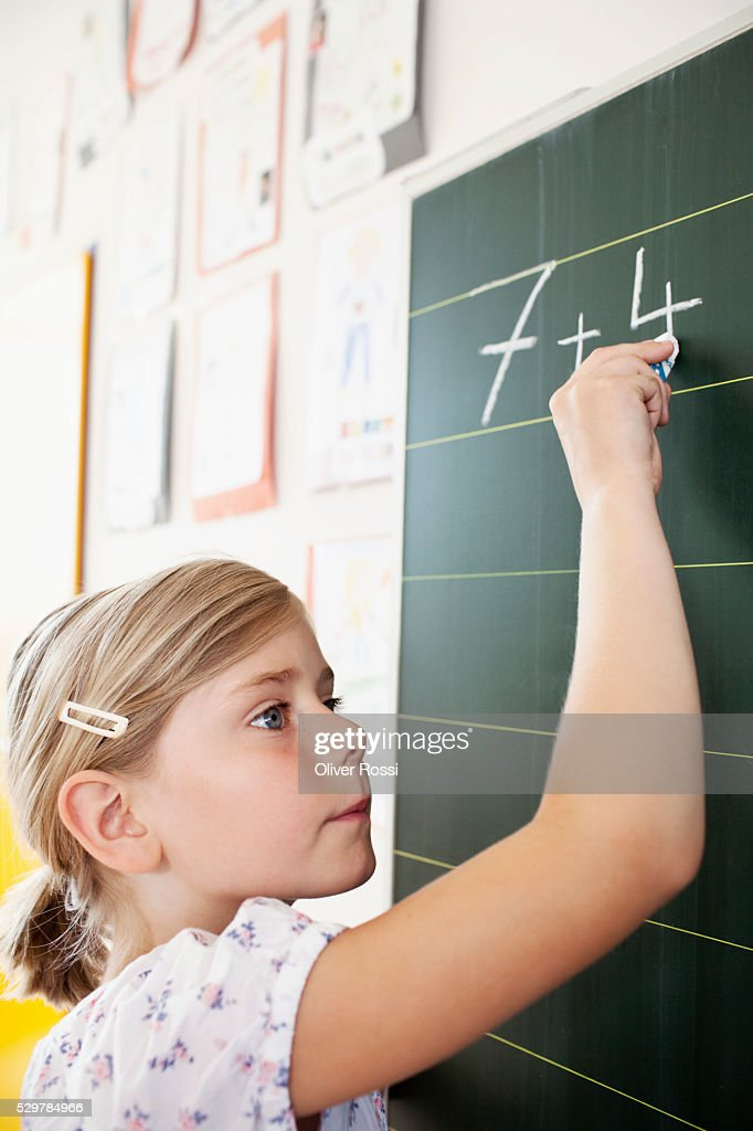 Girl writing on blackboard : Stock-Foto